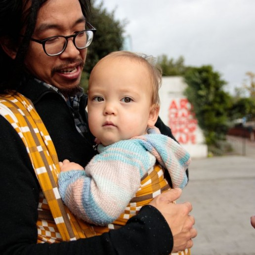 Dad with wrap, dreadlocks small baby benefits of babywearing